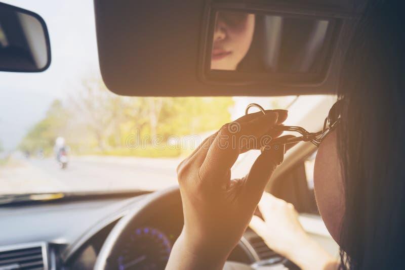 Maquillaje de la mujer su cara usando el bigudí de la pestaña mientras que conduce el coche foto de archivo