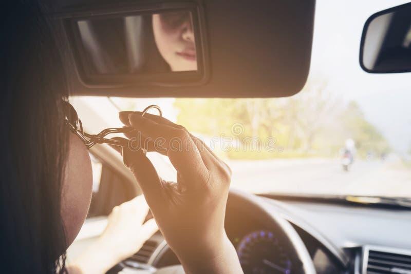 Maquillaje de la mujer su cara usando el bigudí de la pestaña mientras que conduce el coche imagenes de archivo