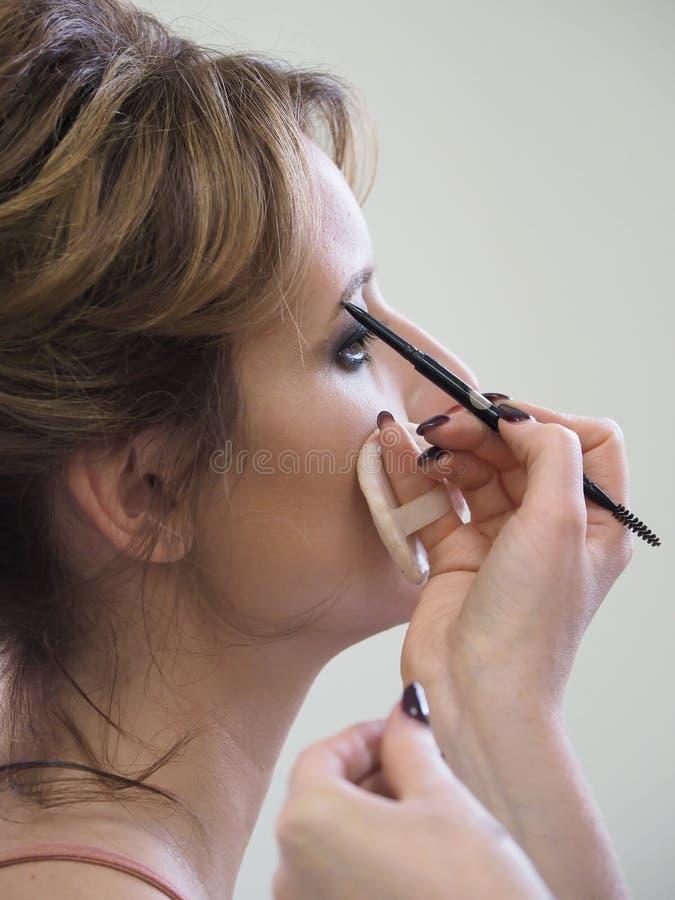 Maquillaje femenino con el lápiz de ceja Cierre para arriba foto de archivo libre de regalías