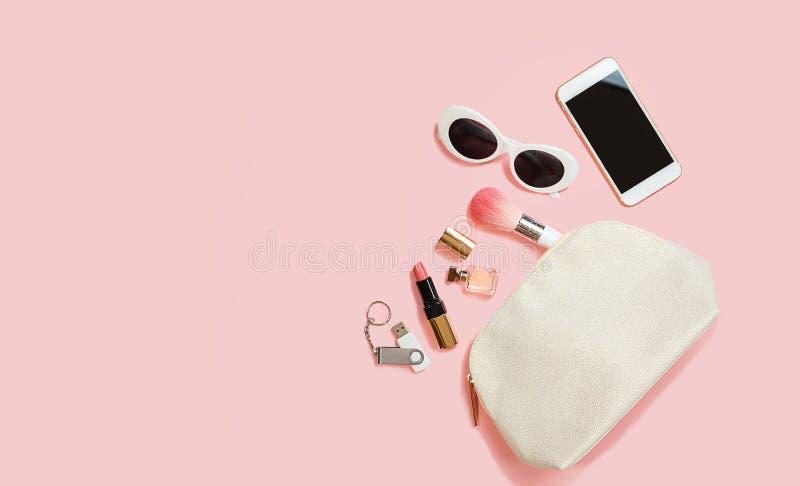 Maquillaje femenino puesto plano de memoria USB de los auriculares del teléfono móvil de las gafas de sol de los cosméticos de lo fotografía de archivo libre de regalías