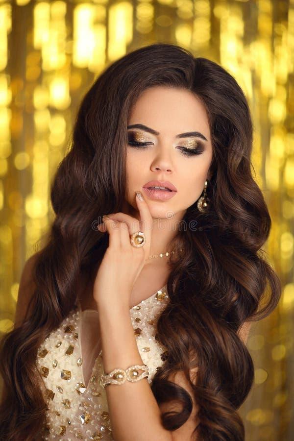 maquillaje Mujer morena elegante en oro forme la joyería Ha ondulada foto de archivo libre de regalías