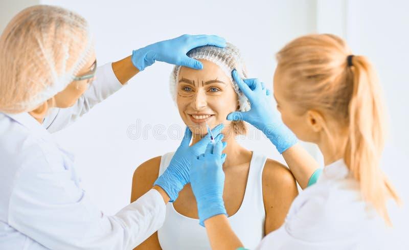 Maquillaje permanente para las cejas Mujer hermosa con las frentes gruesas en salón de belleza Cosmetólogo Doing Eyebrow Tattooin foto de archivo libre de regalías