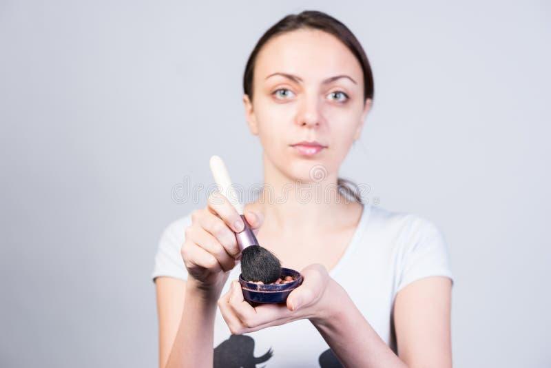 Maquillaje pulverizado tenencia y cepillo de la mujer joven foto de archivo