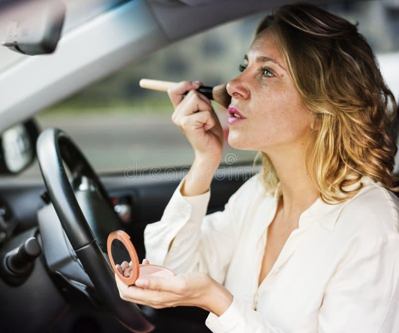 Maquillaje que lleva de la mujer en un coche fotografía de archivo
