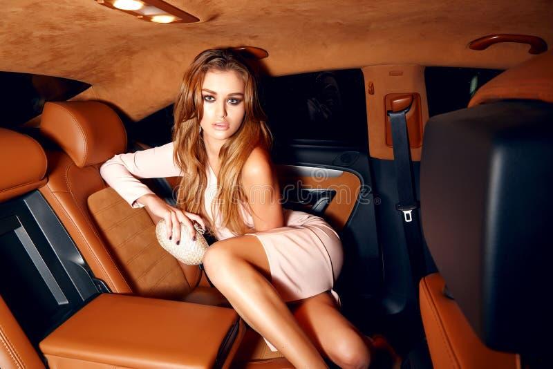 Maquillaje rubio atractivo joven hermoso de la tarde que lleva en la sentada elegante de moda del vestido elegante de la colocaci imagen de archivo libre de regalías
