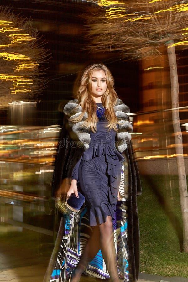 Maquillaje rubio atractivo joven hermoso de la tarde que lleva en stre costoso elegante de moda de la noche del paseo del abrigo  fotos de archivo libres de regalías