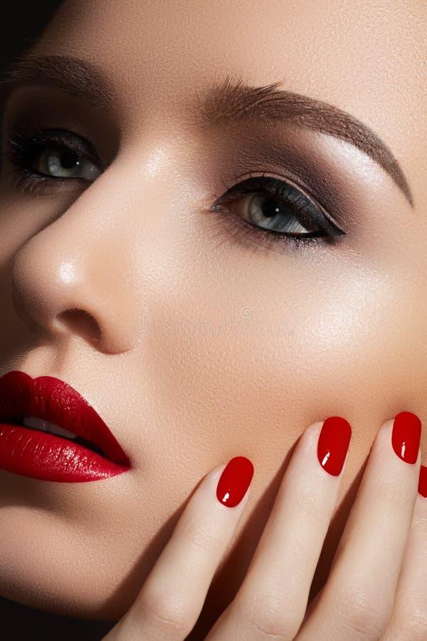 Maquillaje y manicura de la manera. Labios rojos atractivos, clavos fotografía de archivo