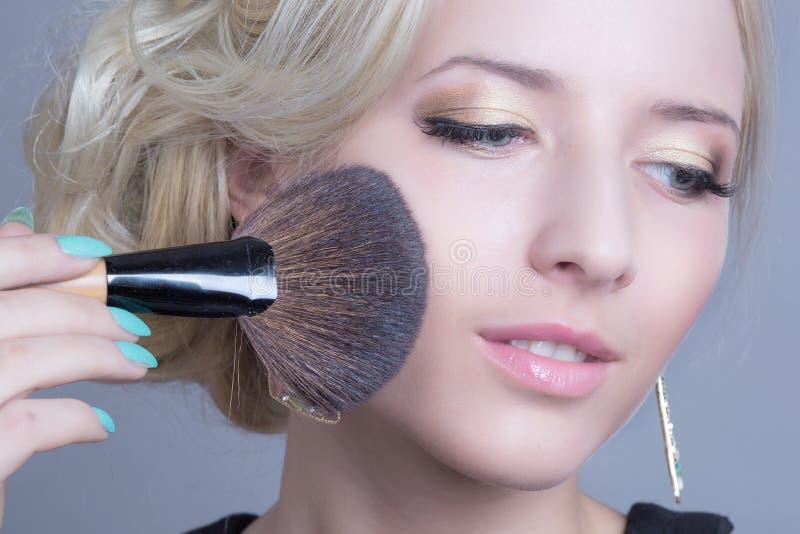 Maquilleur appliquant la poudre de visage image libre de droits