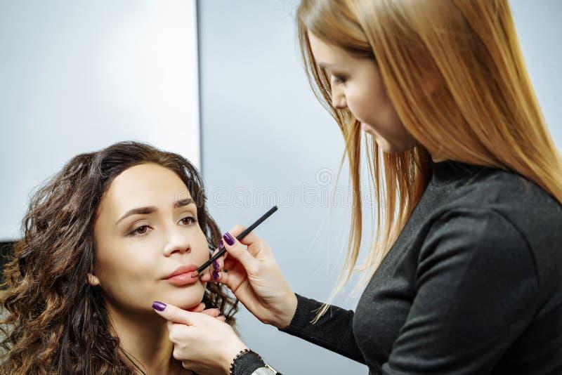 Maquilleur appliquant le rouge à lèvres aux lèvres d'un beau modèle images libres de droits