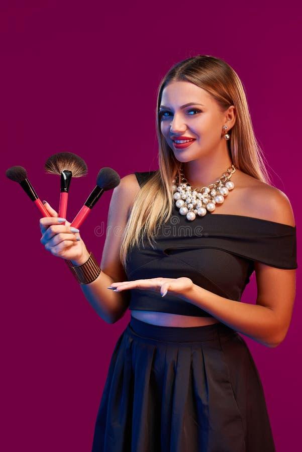 Maquilleur de femme se tenant avec des brosses image stock