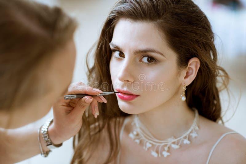 Maquilleur de mariage faisant une jeune mariée de compensation photographie stock libre de droits