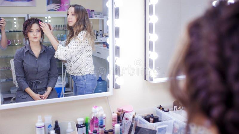 Maquilleur de styliste faisant le maquillage et les cheveux dans un salon de beauté Renivellement professionnel image libre de droits