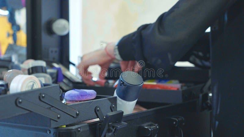 Maquilleur professionnel sélectionnant des outils et des cosmétiques dans la valise de maquillage images libres de droits