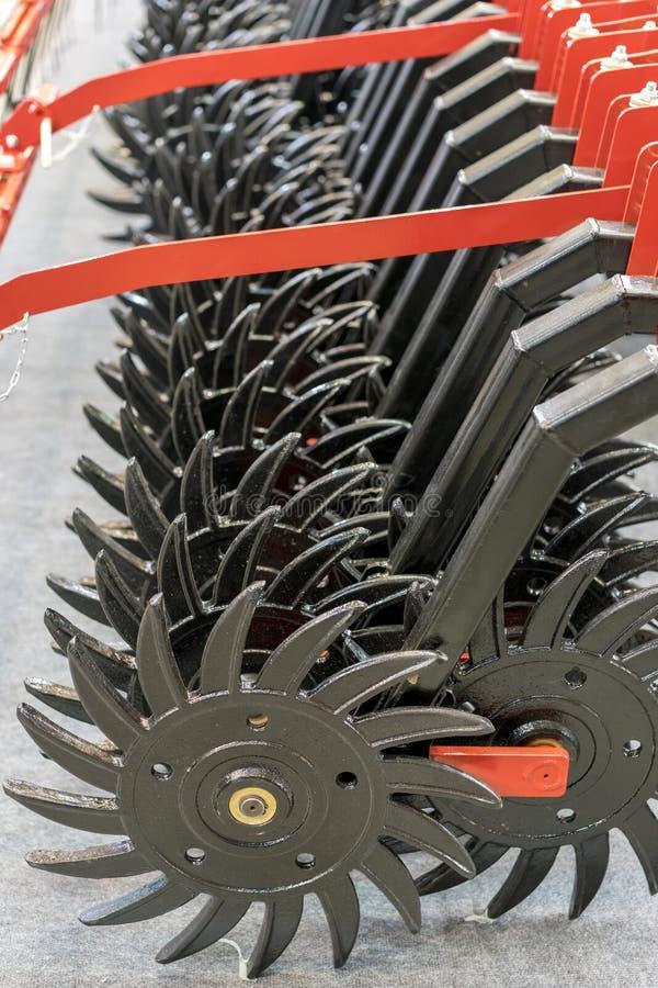 Maquinaria agrícola, modelo do cultivador na exposição Fim vermelho do trator da tecnologia moderna do arado acima em um campo ag imagem de stock royalty free