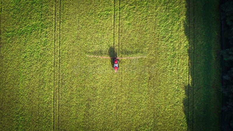 Maquinaria agrícola no campo Trator com um pulverizador Silhueta do homem de negócio Cowering fotografia de stock royalty free
