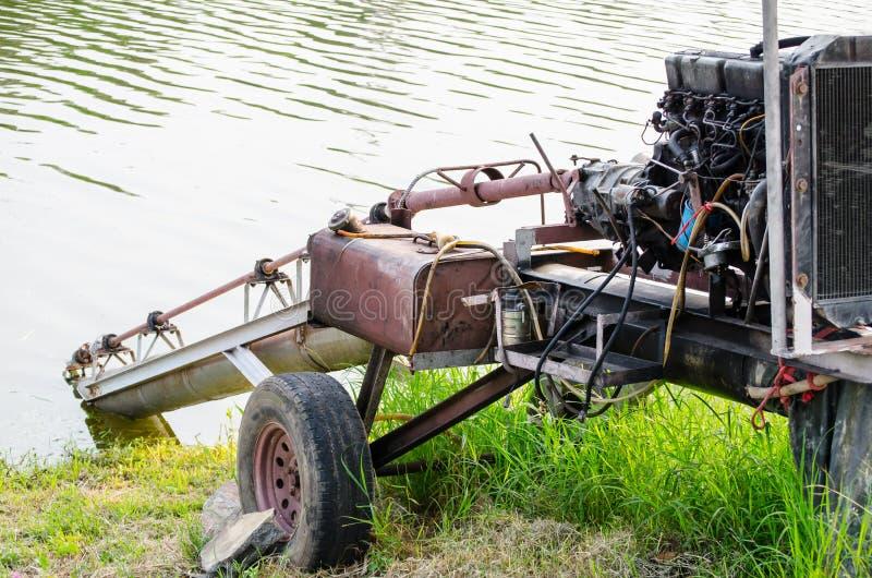 Maquinaria agrícola para el agua de bombeo a una tierra del suelo fotografía de archivo