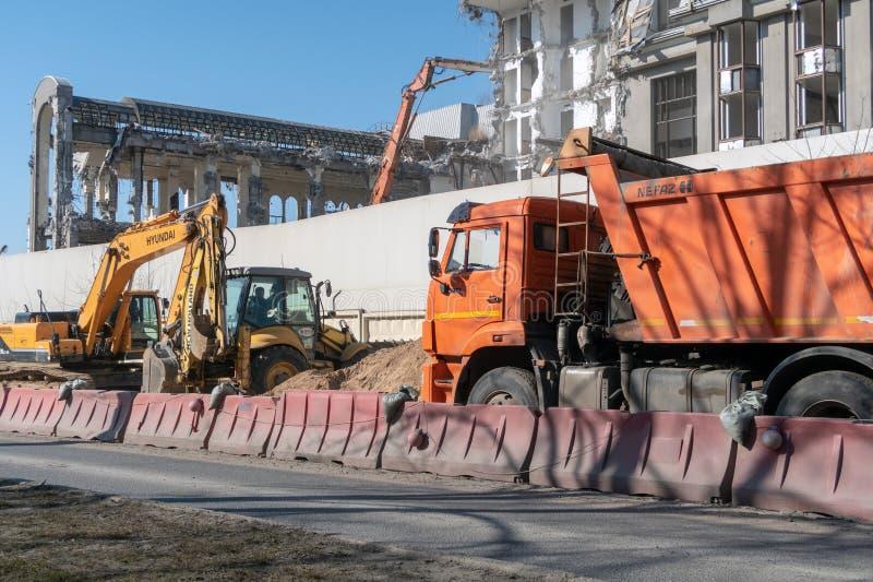 Maquinaria da construção e da estrada: uma máquina escavadora e um caminhão basculante em um canteiro de obras para a demolição d foto de stock