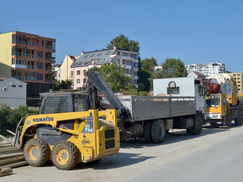 A maquinaria de construção está no lado da estrada no local de trabalhos de construção de estradas imagens de stock
