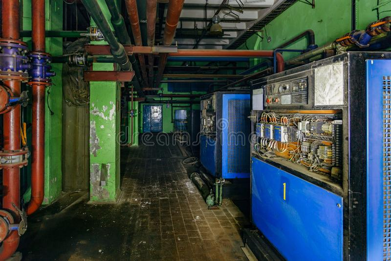 Maquinaria eléctrica vieja en sótano subterráneo oscuro y espeluznante de la fábrica abandonada imagen de archivo libre de regalías
