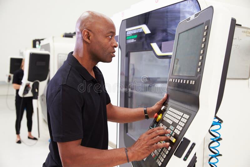 Maquinaria masculina del CNC de Operating del ingeniero en piso de la fábrica imagen de archivo