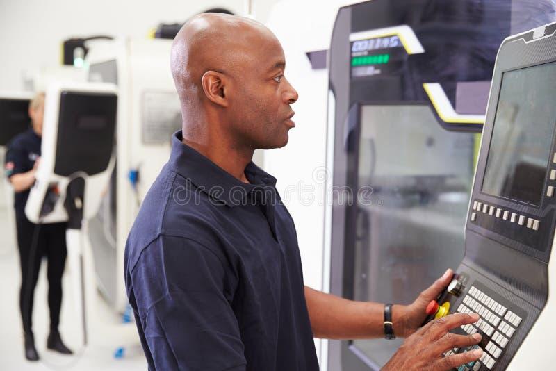 Maquinaria masculina del CNC de Operating del ingeniero en piso de la fábrica imagen de archivo libre de regalías