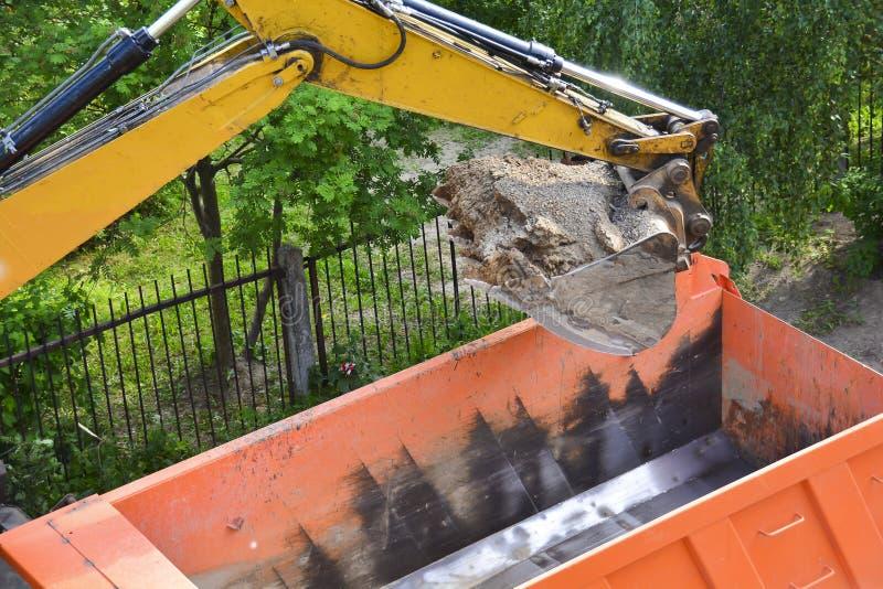 Maquinaria pesada que trabaja en el emplazamiento de la obra - camiones volquete cargados del excavador durante obras por carrete fotos de archivo libres de regalías