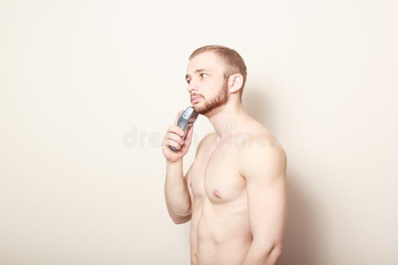 Maquinilla de afeitar eléctrica del afeitado barbudo del individuo fotos de archivo libres de regalías
