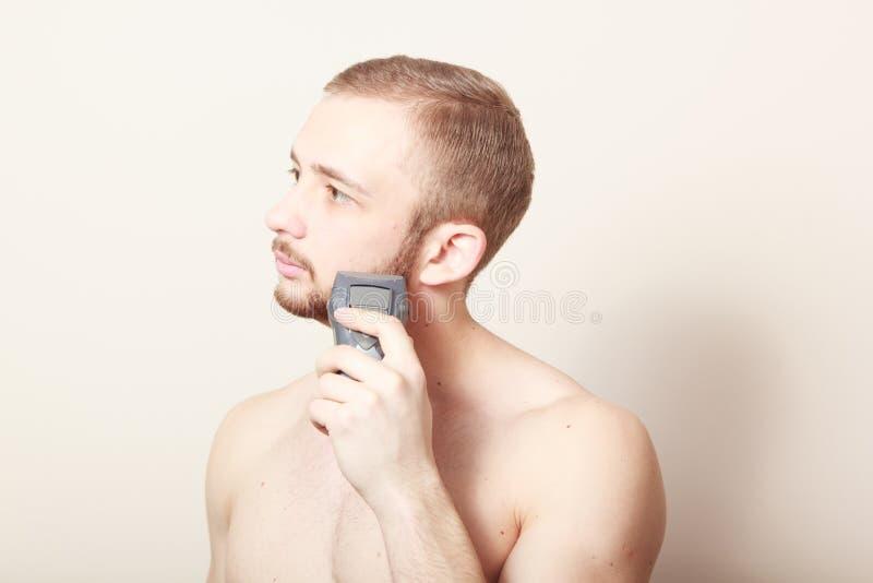 Maquinilla de afeitar eléctrica del afeitado barbudo del individuo imagenes de archivo