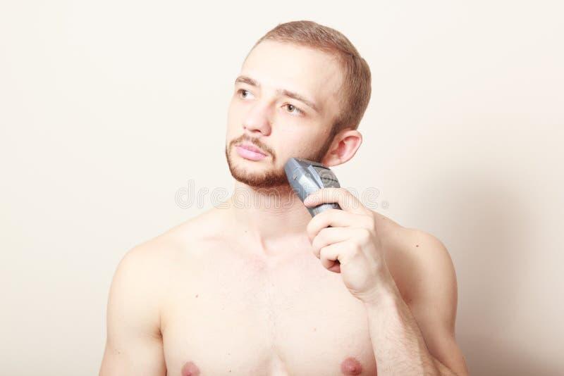 Maquinilla de afeitar eléctrica del afeitado barbudo del individuo imagen de archivo