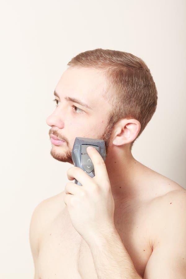 Maquinilla de afeitar eléctrica del afeitado barbudo del individuo fotografía de archivo