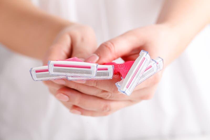Maquinillas de afeitar femeninas rosadas en manos en el fondo blanco Sistema de maquinillas de afeitar en el fondo blanco Maquini imagen de archivo libre de regalías