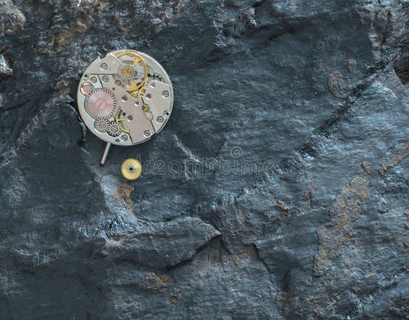 Maquinismo de relojoaria desmontado em uma pedra preta fotografia de stock royalty free