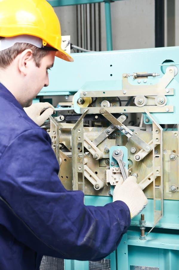 Maquinista con la llave inglesa que ajusta el mecanismo de la elevación imágenes de archivo libres de regalías