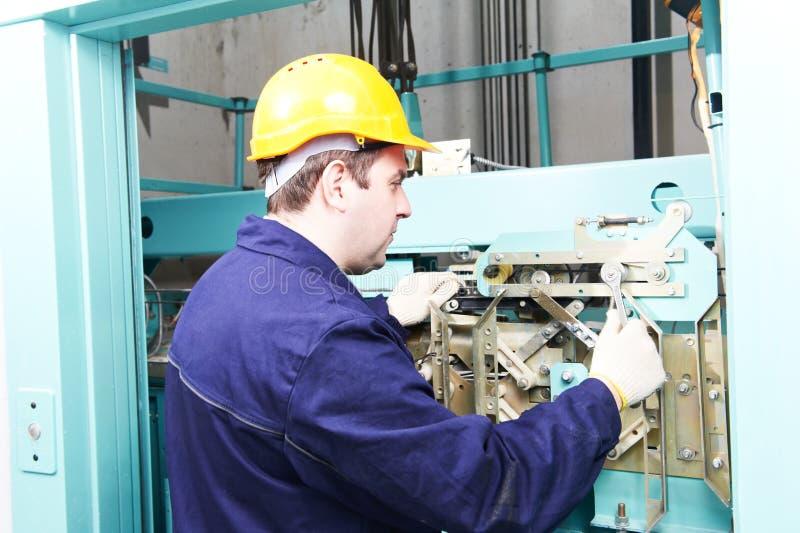 Maquinista con la llave inglesa que ajusta el mecanismo de la elevación foto de archivo
