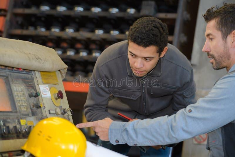 Maquinista que muestra cuerdas al nuevo trabajador imagen de archivo libre de regalías