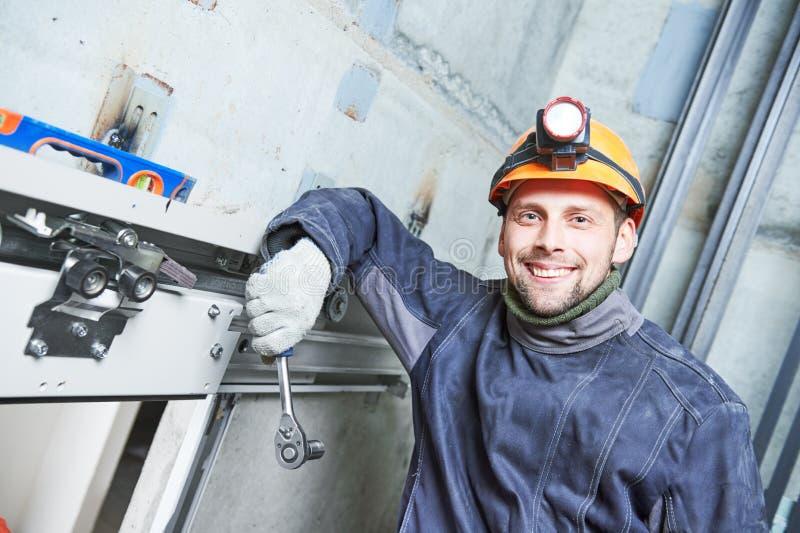 Maquinista sonriente con la llave inglesa que ajusta la elevación en eje de elevador fotografía de archivo