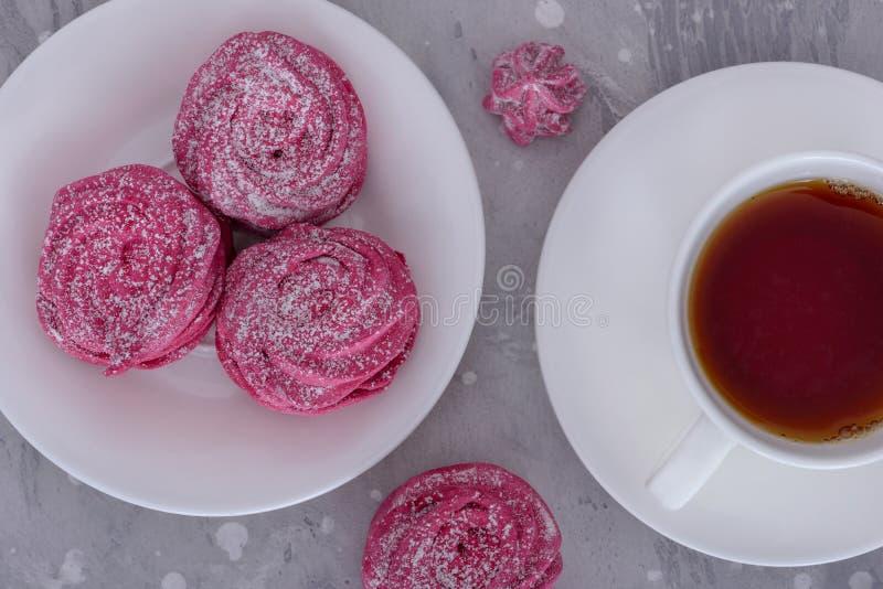Marängar på varmt te för platta och för kopp royaltyfri bild