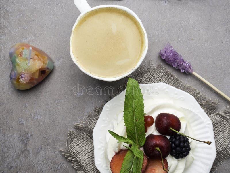 MarängefterrättPavlova kaka med nya bär på en platta och en kopp kaffe Stenbakgrund, närbild royaltyfri fotografi