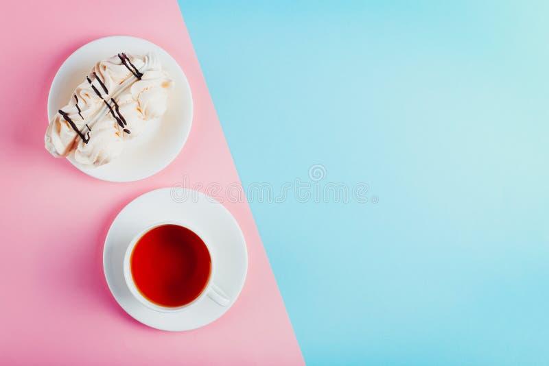 Marängkaka på ett tefat och en kopp te på pastellfärgad kulör pappers- bakgrund kopiera avstånd royaltyfri fotografi