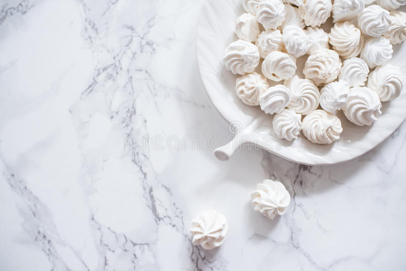 Marängkakor in i en platta på en vit marmor arkivfoto