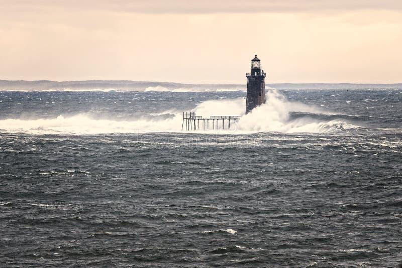 A maré alta original faz com que as ondas enormes quebrem contra Ligh distante fotos de stock