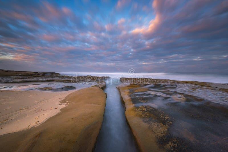 Maré alta que apressa-se em um canal ao longo da praia imagem de stock