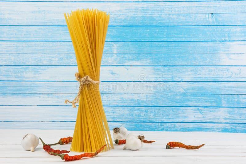 Maré italiana deliciosa fresca dos espaguetes da massa junto com o laço do fluxo natural do Grunge com bio pimentas vermelhas fre fotografia de stock