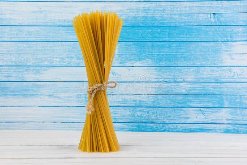Maré italiana deliciosa fresca dos espaguetes da massa junto com o laço do fluxo natural do Grunge em velho Textured de madeira b imagens de stock
