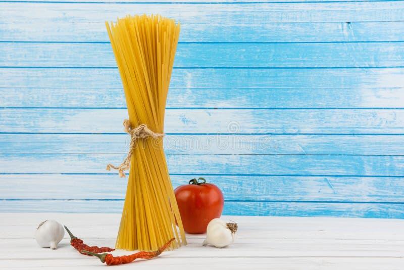 Maré italiana deliciosa fresca dos espaguetes da massa junto com o laço do fluxo natural do Grunge com os pimentões vermelhos do  imagem de stock royalty free