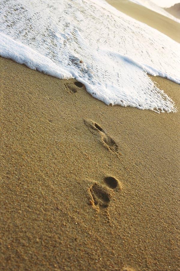 A maré que lava sobre uma cópia do pé cobriu a praia imagem de stock