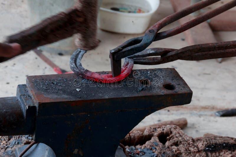 Maréchal-ferrant faisant le fer à cheval photographie stock