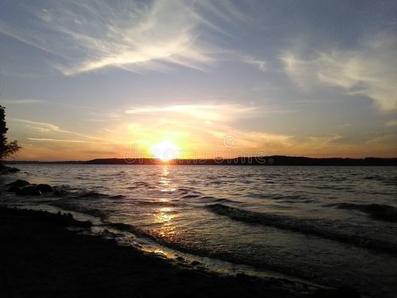 Marées dedans et le coucher du soleil photographie stock libre de droits