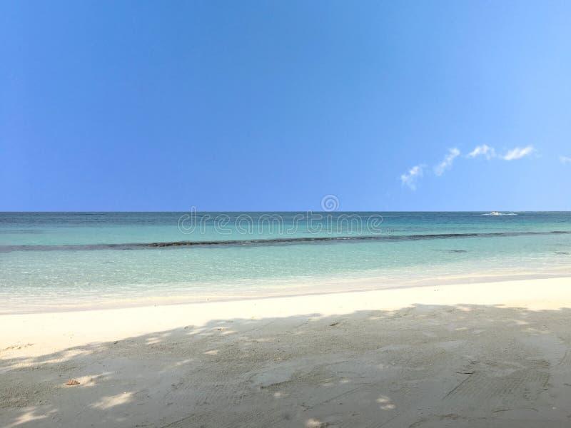 Mar azul calmo bonito e areia branca na praia sob o céu azul imagem de stock