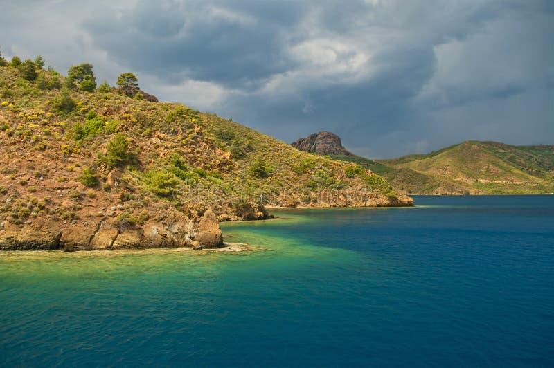 Mar azul em torno das ilhas rochosas ensolarados no dia tormentoso imagem de stock royalty free